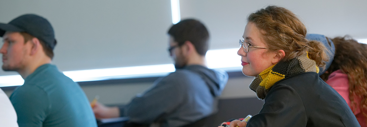 A student listening to a lecture in a classroom