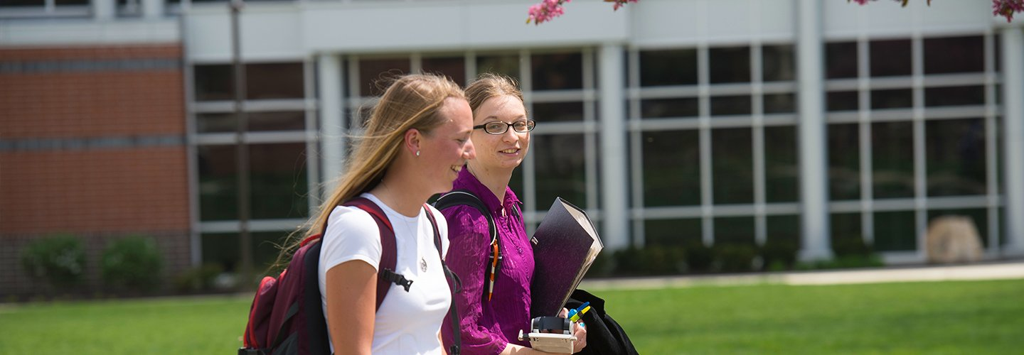 Two students walking together between classes on campus.